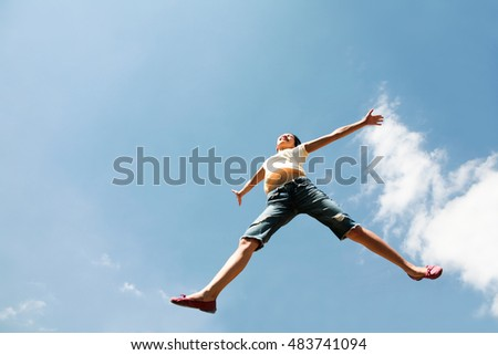 View from below of leaping happy girl on the background of blue sky