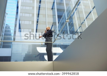 View from below of young male financier dressed in luxury suit is phoning via cell telephone during work break in company. Intelligent businessman is talking with international partner on mobile phone - stock photo