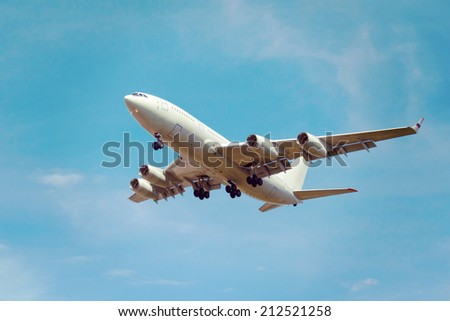 view from below on the white jet passenger aircraft with the gear on the background the blue sky - stock photo
