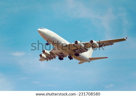 view from below on the white jet passenger aircraft with the gear on the background the blue sky