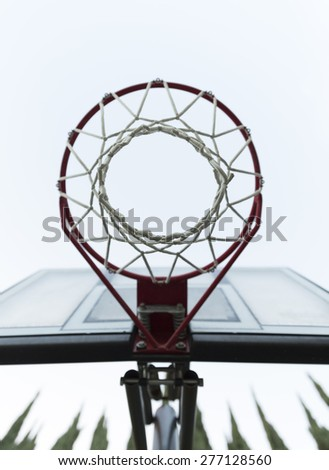 View from Bottom of the Basketball Hoop against White Sky - stock photo