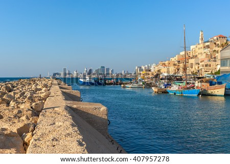 View from breakwater on small port with boats, old Jaffa and Tel Aviv on background under blue sky in Israel. - stock photo