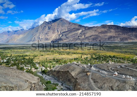 View from buddhist monastery Diskit Gompa on Himalaya mountains with green fields and small tibetan village in Nubra valley, Ladakh, India