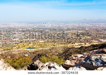 View from Dobbin's Point on South Mountain in Phoenix, Arizona with rocks in foreground and cityscape in background - stock photo