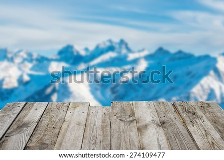 View from empty wooden deck table to the sunny winter mountains in bokeh