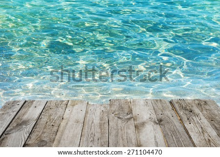View from empty wooden deck table to tropical sunny beach with blue water background - stock photo
