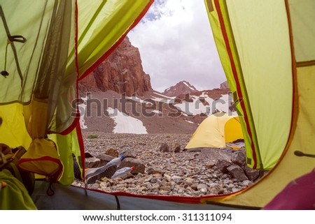 View from Green Tent. Mountain Landscape from Camping Tent Vanishing Point Steep Rocky Terrain and Hiking Boots Gear - stock photo