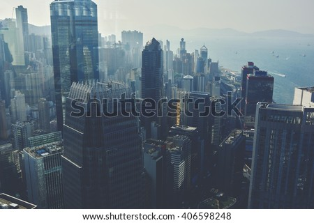 View from high on a business center with high skyscrapers and sea with floating yachts. Modern developed metropolitan city with office and commercial buildings with contemporary architecture  - stock photo