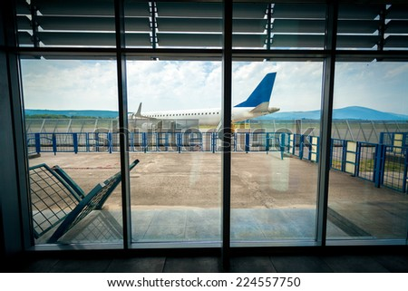 View from inside of airport terminal on the plane on runway - stock photo