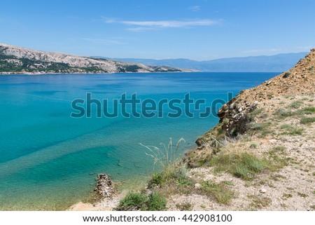 View from Krk island towards mountain Velebit / Beautiful summer seascape at Adriatic sea / Mediterranean seascape / Summer in Baska, Krk, Croatia / Turquoise sea water - stock photo