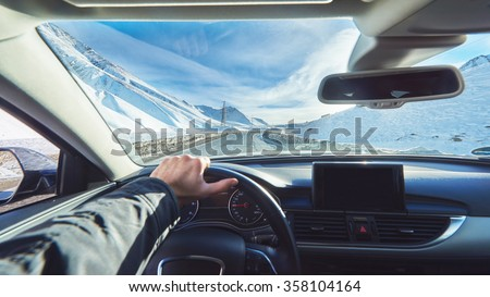 view from luxury car inside with part of interior gps screen with driver male hand on  the steering wheel during bright snowy sunny day on straight ice road with snowy mountains in background  - stock photo