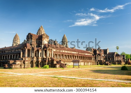 View from one of outside corners of ancient temple complex Angkor Wat in Siem Reap, Cambodia. Blue sky in background. Mysterious Angkor Wat is a popular tourist attraction. - stock photo