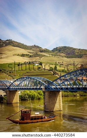 View from Pinhao village in Portugal to Douro valley, river with boat and bridge - stock photo