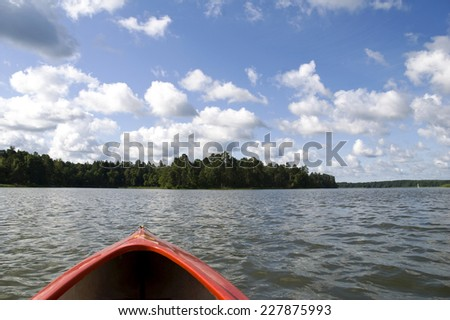 View from red kayak at Nidzkie lake in Ruciane-Nida, Masuria lake district in Poland, Europe. Cumulus clouds on sunny blue sky and woods afar landscape, Polish Jezioro Nidzkie. Horizontal orientation