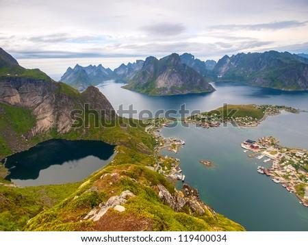 View from Reinebringen on the fishing village Reine at Moskenesoya, Lofoten with the fjord Kjerkfjord in the background. - stock photo