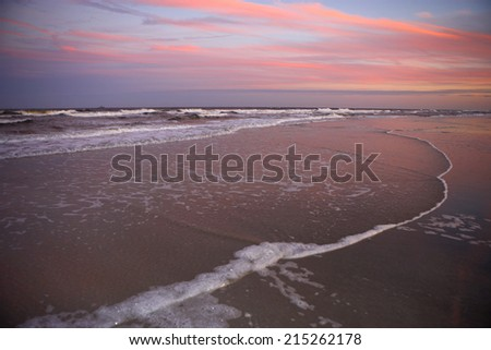 View from sandy beach of picturesque sunset, horizon over sea, surf lapping on shore - stock photo