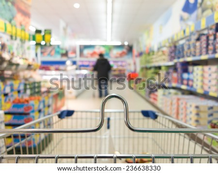 View from shopping cart trolley basket at supermarket self-service grocery shop. Retail. Blurred background. - stock photo