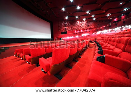 View from stairs on rows of comfortable red chairs in illuminate red room cinema