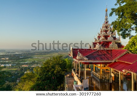 View from Su Taung Pyai Pagoda at Mandalay hill down to the lowlands at sunset - stock photo