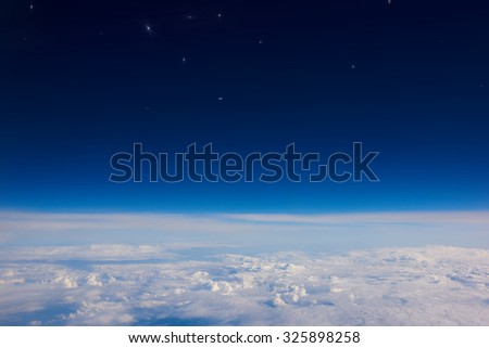 View from the airplane of a fluffy white clouds and blue sky with stars background with copy space for your text message or information content, advertising field - stock photo