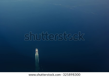 View from the airplane of a movement a big ship on the ocean background with copy space for your text message or information content, advertise field - stock photo