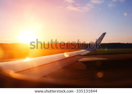 View from the airplane window on a runway before take off. Beautiful sunset or sunrise view. - stock photo