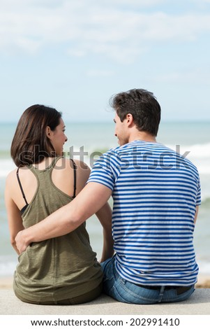 View from the back of a young couple enjoying a romantic day at the beach sitting on a wall overlooking the ocean arm in arm and smiling at each other - stock photo