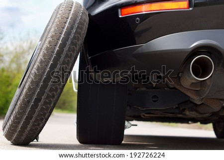 View from the back of the vehicle showing the exhaust pipe of a spare tyre balanced against a car - stock photo