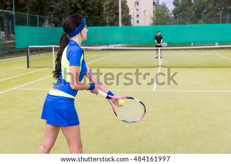 View from the back on a female tennis player wearing a sportswear playing tennis on a court outdoor in summer
