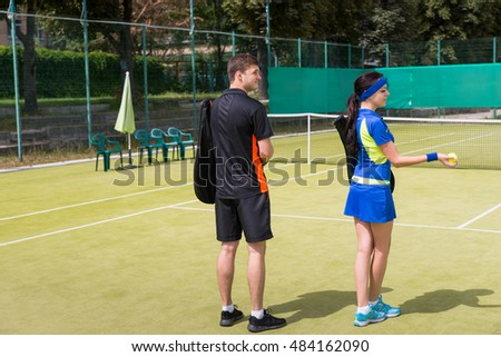 View from the back on two young tennis players wearing a sportswear with black covers for racket on their shoulders, on a court outdoor in summer or spring