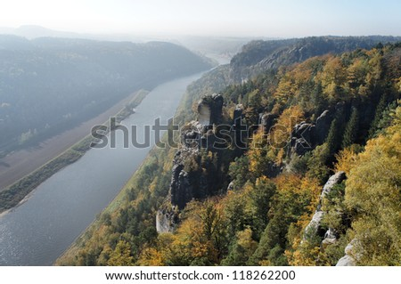 View from the Bastei-Bridge in Saxon Switzerland in Germany on the Elbe River downstream; a sunny autumn day; backlit subject/ View on the Elbe downstream