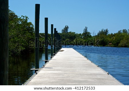 View from the beginning of a long pier or boat dock  on Imperial River in Bonita Springs, Florida.