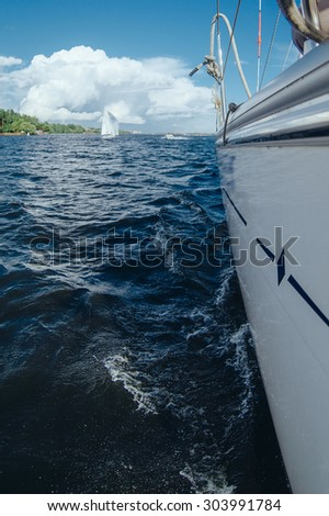 View from the board of a sailing yacht on the waters, sailing ships and the forest growing along the coast, as well as people's homes. Aboard the yacht inside waves lake - stock photo