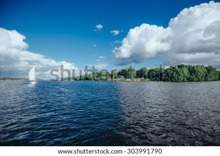 View from the board of a sailing yacht on the waters, sailing ships and the forest growing along the coast, as well as people's homes. The boat floating on the lake - stock photo