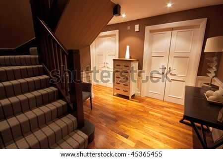 View from the bottom of a staircase of a wooden floored hallway in a luxury home. - stock photo