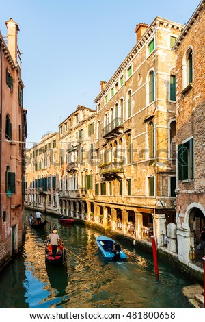 View from the bridge on the small canals in Venice. Beautiful scenic street with water and boats. Bright colorful houses on the water. Italy.
