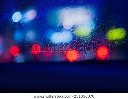 View from the car in rainy night, looking on blurry glowing cars lights through windscreen, automobile traffic in nighttime - stock photo