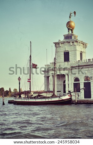 View from the Grand Canal on an yacht and Dogana da Mar ( Dogana di Mare) building where the Grand Canal meets the Giudecca Canal in Venice, Italy. Filtered image, vintage effect applied - stock photo