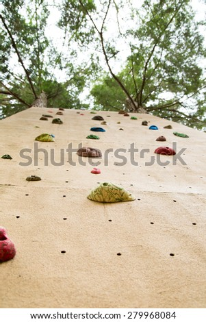 view from the ground looking up at an outdoor climbing wall.  Implies concept of facing challenge and heading upwards - stock photo