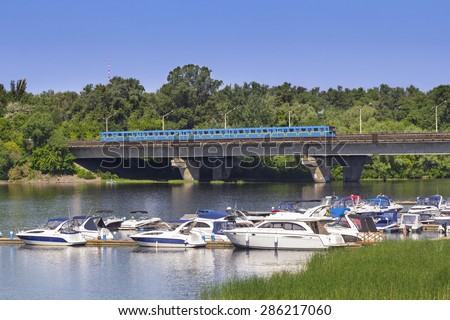 View from the left bank of Kiev - the metro brigde on Dnieper river and a moorage of motor boats - stock photo