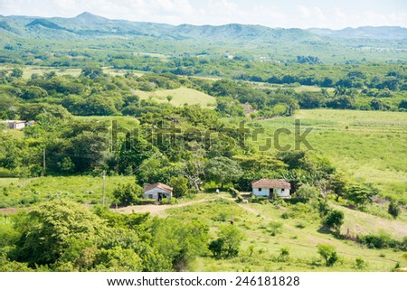 View from the Manaca Iznaga tower, beautiful Cuban countryside featuring the Escambray mountain range, the green farms and a full of clouds sky - stock photo