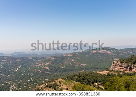 View from the Monastery Sant Llorenc del Muntis, on top of La Mola, a rocky mountain massif near Barcelona, to the mountain of Montserrat. The Mountain is very famous due the church and the Monastery - stock photo