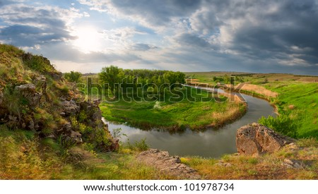 View from the mountain on the river, the wood and a meadow, shined with a bright sun - stock photo