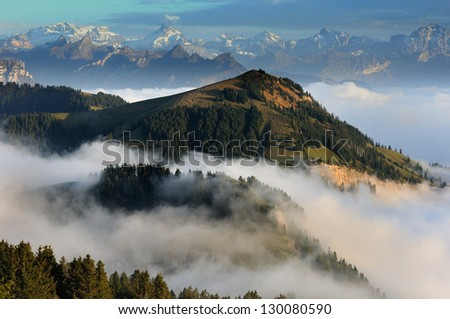 View from the mountain Rigi, Switzerland, with clouds below and snowy tops on the background