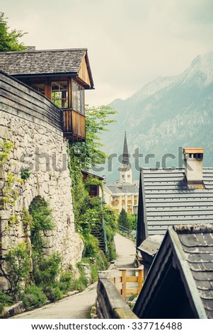 View from the narrow street  on the village, church and wooden houses with small balconies.  Hallstatt, Austria historical village the Hallstatter lake and promoted by UNESCO World Heritage region. - stock photo