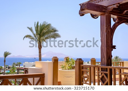View from the outdoor patio a luxury seaside resort looking out over palm trees and beach umbrellas to a calm blue ocean, conceptual of a summer vacation - stock photo