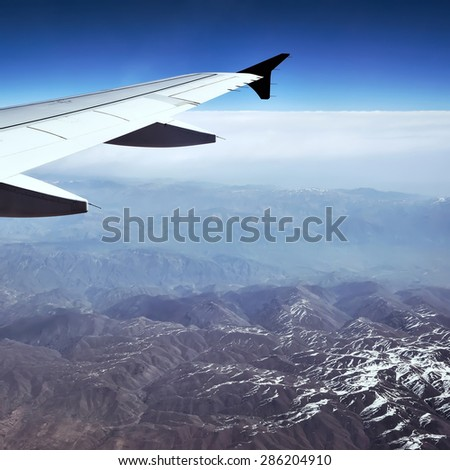 view from the plane, blue sky and mountains  in the window - stock photo