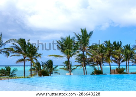 view from the poolside swimming pool of palm trees and the ocean with clouded blue sky - stock photo