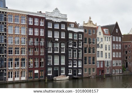 View from the Prins Hendrikkade street in Amsterdam to the old historical dutch buildings near the water. Netherlands.