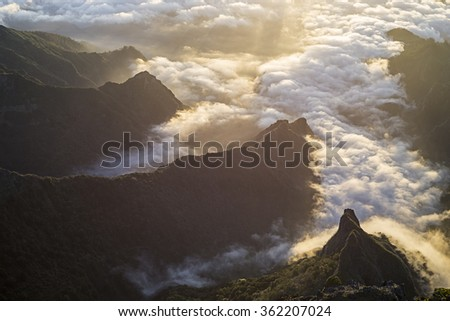 View from the summit on Mount Pico do Arieiro over steep cliffs and high peaks with the morning mist still covering the canyons and rugged valleys of the mountains in central Madeira during sunrise